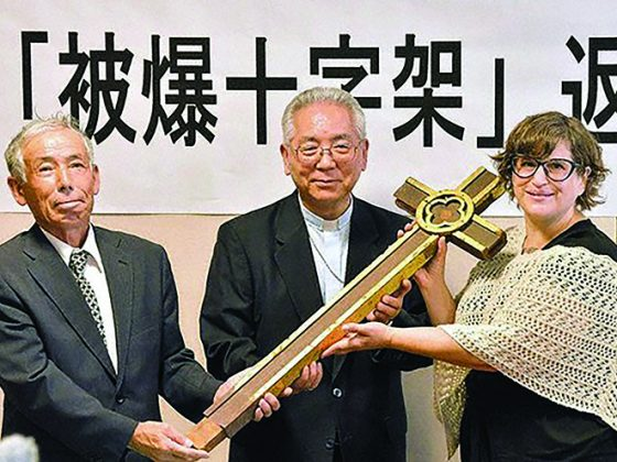 From right, Tanya Maus, the director of the Peace Resource Center at Wilmington Colleg; Archbishop of Nagasaki Mitsuaki Takami; and Chitose Fujita, a member of the congregation at Urakami Cathedral, smile with the cross that was returned to the cathedral in the city of Nagasaki on Aug. 7, 2019. (Mainichi/Noriko Tokuno)